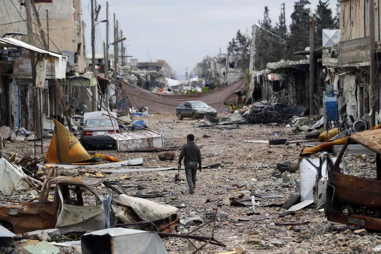 A man walks in a street with abandoned vehicles and and damaged buildings in the northern Syrian town of Kobani January 30, 2015. REUTERS/Osman Orsal