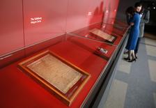 A woman looks at the four surviving original copies of the 1215 Magna Carta, at the British Library in London February 2, 2015. REUTERS/Stefan Wermuth