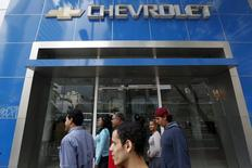 People walk past a closed Chevrolet branch in Caracas January 30, 2015.  REUTERS/Carlos Garcia Rawlins
