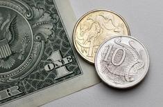 Монеты австралийской валюты на купюре номиналом один доллар США в Сиднее 27 июля 2011 года. Курс австралийского доллара снизился до шестилетнего минимума после снижения процентных ставок центробанка Австралии. REUTERS/Tim Wimborne