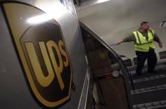 Un trabajador de UPS descarga paquetes desde un camión en Rockford. Imagen de archivo, 9 diciembre, 2014. United Parcel Service Inc reportó el martes una ganancia trimestral ligeramente inferior tras una temporada decepcionante de festividades de fin de año, en la que sus costos fueron más altos de lo esperado. REUTERS/Jim Young