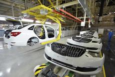 An employee looks on next to an assembly production line of Buick cars at a General Motors factory in Wuhan, Hubei province January 28, 2015. REUTERS/Stringer