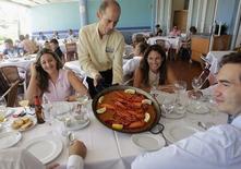 En la foto, un camarero sirve una paella en un restaurante playero en Valencia el 24 de julio de 2014. El sector de servicios español creció en enero a su mayor ritmo en cinco meses, según un sondeo publicado el miércoles, y las empresas contrataron personal con mayor rapidez mientras el país consolida su regreso a la expansión económica. REUTERS/Heino Kalis