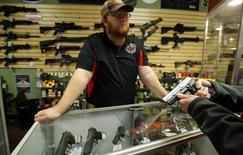Chris Cox, empleado de la tienda de armas Metro Shooting Supplies, conversa con un cliente sobre una pistola de 9 milímetros en Bridgeton, EEUU, nov 13 2014. Una medición sobre el crecimiento del sector de servicios de Estados Unidos fue mayor a lo esperado en enero, aunque permaneció cerca de mínimos en seis meses debido a que un índice de empleo declinó con fuerza. REUTERS/Jim Young