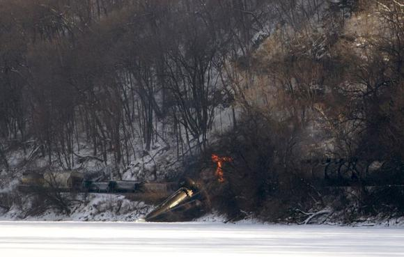 A freight train, owned by Canadian Pacific Railway, carrying ethanol fuel with one car engulfed in flames, sits on the banks of the Mississippi River in a remote location north of Dubuque, Iowa in this February 4, 2015 picture provided by Dubuque Telegraph Herald. CREDIT: REUTERS/MIKE BURLEY/DUBUQUE TELEGRAPH HERALD/HANDOUT