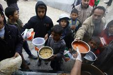 Kurdish refugees from the Syrian town of Kobani wait for food distributed during lunch time at a refugee camp in the border town of Suruc, Sanliurfa province January 31, 2015. REUTERS/Umit Bektas