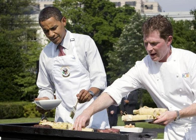 U.S. President Barack Obama stands next to celebrity chef Bobby Flay (R) at the grill as he hosts a barbeque for local school students on the South Lawn of the White House in Washington in this file photo taken on June 19, 2009. REUTERS/Larry Downing