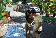Turistas leem placa dedicada a Bob Marley do lado de fora do museu do cantor em Kingston. 13/12/2013 REUTERS/Gilbert Bellamy
