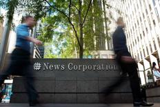 News Corp, el gigante de los medios de Rupert Murdoch, informó el jueves ingresos y ganancias trimestrales por encima del promedio de las estimaciones de los analistas, gracias a que sus florecientes negocios editorial e inmobiliario contrarrestaron las menguantes ventas de periódicos. En la imagen, dos personas pasan junto a la sede de la firma en Nueva York en una fotografía de archivo.  REUTERS/Keith Bedford/Files