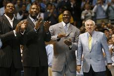 Former University of North Carolina players Sam Perkins, James Worthy, and Michael Jordan, along with former North Carolina head basketball coach Dean Smith (L-R) watch a presentation honoring the 1957 and 1982 national championship teams at halftime of the NCAA basketball game between North Carolina and Wake Forest University in Chapel Hill, North Carolina, in this file photo taken February 10, 2007.  REUTERS/Ellen Ozier/Files