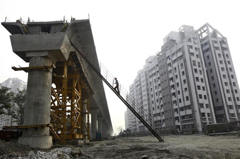 A worker climbs up to a pillar of a metro railway under construction in Kolkata February 9, 2015. REUTERS/Rupak De Chowdhuri/Files