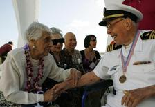 Joann Olsen (L) shares a light hearted moment with USS Arizona survivor Joseph Langdell (R) after the internment ceremony of her husband, USS Arizona survivor Vernon J. Olsen, aboard the USS Arizona Memorial during the 70th anniversary of the attack on Pearl Harbor at the World War II Valor in the Pacific National Monument in Honolulu, Hawaii December 7, 2011. REUTERS/Hugh Gentry