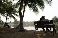 Couples sit at a park in Bangkok February 11, 2015. REUTERS/Athit Perawongmetha