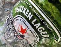 Бутылка пива Heineken в Сингапуре. 10 мая 2012 года. Третья крупнейшая пивоваренная компания мира Heineken ждет замедления роста продаж и рентабельности в 2015 году после успешного прошлого года, по итогам которого она резко повысила дивиденды благодаря расширению на развивающихся рынках и футбольному чемпионату мира. REUTERS/Matthew Lee