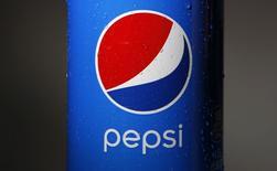 Логотип  Pepsi на бутылке в Уилметте, Иллинойс 10 февраля 2015 года. PepsiCo Inc отчиталась о превысившей прогнозы прибыли в четвертом квартале благодаря росту продаж снэков подразделением Frito-Lay и сообщила о возможном обратном выкупе акций объемом до $12 миллиардов к 2018 году. REUTERS/Jim Young