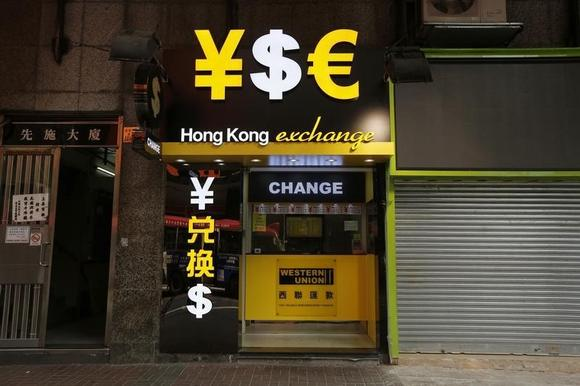 Signs of the Chinese yuan, U.S. dollar and euro are seen at a currency exchange in Hong Kong October 16, 2014.  REUTERS/Bobby Yip