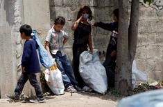 Syrian refugee children collect plastics as they stand along a street in south of Sidon, southern Lebanon June 10, 2014. REUTERS/Ali Hashisho