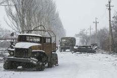 Грузовик пророссийских ополченцев проезжает мимо подбитой машины украинской армии в Углегорске 16 февраля 2015 года. Подконтрольный Киеву город Дебальцево на востоке Украины подвергся интенсивному артиллерийскому обстрелу в понедельник, несмотря на прекращение огня накануне. Пророссийские сепаратисты отказались соблюдать перемирие в окрестностях крупного транспортного узла и говорят, что намерены взять его под контроль, предлагая украинской армии уйти, оставив вооружения. REUTERS/Baz Ratner