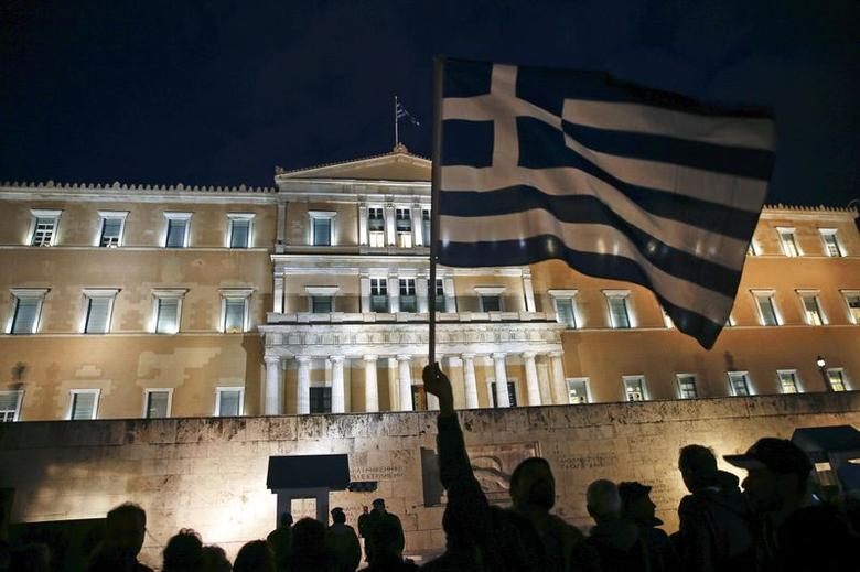 A protester waves a Greek national flag during an anti-austerity pro-government demonstration in front of the parliament in Athens February 16, 2015. REUTERS/Yannis Behrakis
