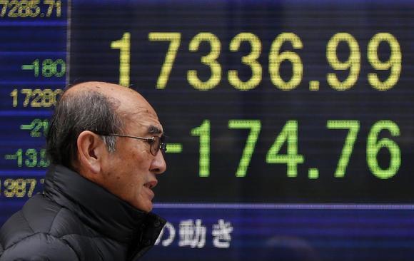 A man walks past an electronic board showing Japan's Nikkei average outside a brokerage in Tokyo January 26, 2015. REUTERS/Yuya Shino