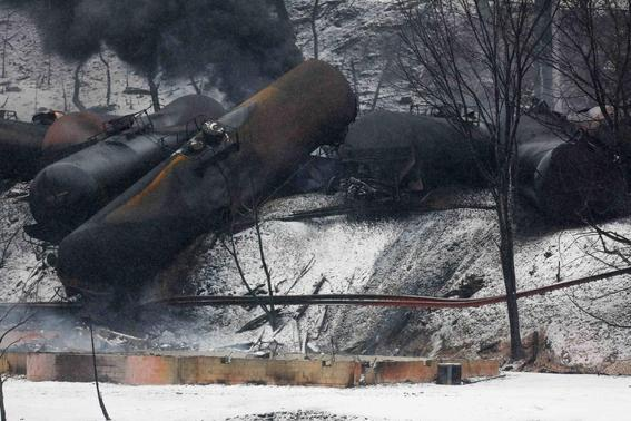 The charred remains of a house and a vehicle are shown below a derailed CSX Corp train in Mount Carbon, West Virginia, Tuesday, February 17, 2015. REUTERS-Marcus Constantino