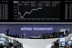 Traders are pictured at their desks in front of the DAX board at the Frankfurt stock exchange February 17, 2015. REUTERS/Staff/remote