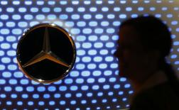 A journalist is silhouetted against a car bonnet emblem of a Mercedes-Benz car at the annual news conference of Daimler AG in Stuttgart February 5, 2015.   REUTERS/Ralph Orlowski
