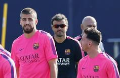 FC Barcelona's coach Luis Enrique (C) looks at his players Gerard Pique (L) and Lionel Messi (R) during a training session at Joan Gamper training camp, near Barcelona August 5, 2014. REUTERS/Albert Gea/Files