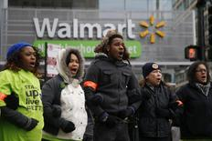 Protesters outside a Wal-Mart store link arms in the street before being removed by police during a demonstration for higher wages and better working conditions in Chicago, in this file photo taken November 28, 2014. REUTERS/Andrew Nelles/Files