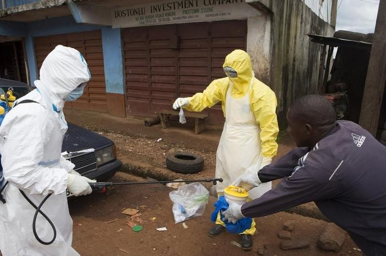 Health workers in protective equipment handle a sample taken from the body of someone who is suspected to have died from Ebola virus, near Rokupa Hospital, Freetown October 6, 2014. REUTERS/Christopher Black/WHO/Handout via Reuters