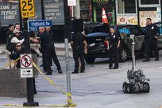 Policiais cercam um veículo enquanto robô deixa o local de uma ameaça de bomba em Hollywood. 19/02/2015 REUTERS/Adrees Latif