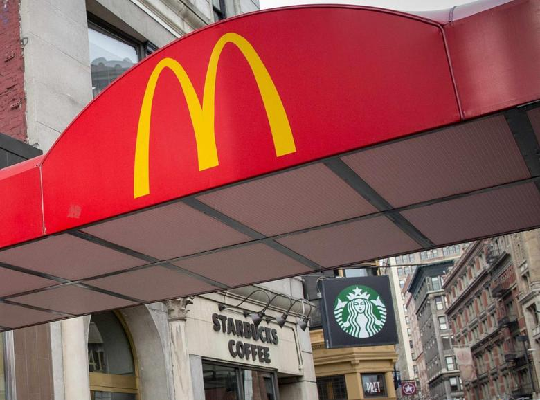 McDonald's Golden Arches are seen next to a Starbucks at the Union Square location in New York January 29, 2015. REUTERS/Brendan McDermid
