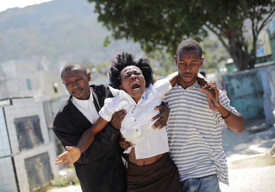 A woman reacts as others help her walk at the cemetery before the funeral for the victims of a Carnival stampede in Port-au-Prince February 21, 2015.  REUTERS-Andres Martinez Casares