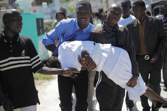 A woman who fainted is helped by others during the funeral for the victims of a Carnival stampede at a cemetery in Port-au-Prince February 21, 2015.  REUTERS-Andres Martinez Casares