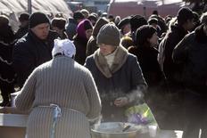 Местные жители на площади города Дебальцево 22 февраля 2015 года. Сотни жителей украинского Дебальцева вышли на улицы из подвалов и бомбоубежищ, в которых они месяц прятались от артиллерийских обстрелов во время осады сепаратистами, впервые с начала конфликта пошедшими на кровопролитный штурм многотысячного города. REUTERS/Baz Ratner
