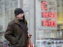 """Мужчина проходит мимо вывески пункта обмена валюты в Москве 11 февраля 2015 года. Рубль начал резким падением биржевые торги вторника в ответ на понижение кредитного рейтинга России агентством Moody""""s и отрицательную динамику нефти на мировых рынках. REUTERS/Sergei Karpukhin"""