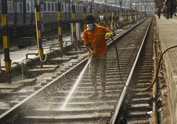 A worker cleans a railway track at a railway station in Kolkata October 2, 2014. REUTERS/Rupak De Chowdhuri/Files