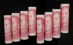 Ilustración fotográfica de billetes de 100 yuanes enrrollados en Pekín, nov 5 2013. Más de 60 bancos centrales tienen yuanes chinos en sus reservas, y esa suma, junto con la de la moneda china en los fondos soberanos de riqueza, debería crecer unos 500.000 millones de dólares en los próximos cinco años, dijeron banqueros enfocados en China el miércoles. REUTERS/Jason Lee