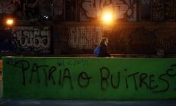 Un grafiti alusivo a la crisis de deuda de Argentina en Buenos Aires, sep 24 2014. Argentina, que tiene virtualmente cerrados los mercados globales de crédito debido a una larga disputa por sus bonos impagos, considera emitir deuda en dólares a largo plazo bajo legislación local, dijo el viceministro de Economía, Emmanuel Álvarez Agis, en una entrevista publicada el miércoles por un diario local.     REUTERS/Marcos Brindicci