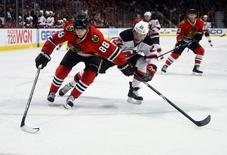 Chicago Blackhawks right wing Patrick Kane (88) skates with the puck against New Jersey Devils defenseman Eric Gelinas (22) during the third period at the United Center. The Chicago Blackhawks defeat the New Jersey Devils 3-1. Mandatory Credit: Mike DiNovo-USA TODAY Sports