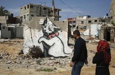 Palestinos em frente mural supostamente pintado por Banksy, em Gaza. 26/02/2015 REUTERS/Suhaib Salem
