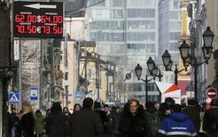 Вывеска пункта обмена валюты в Москве. 24 февраля 2015 года. Рубль торгуется с умеренными отрицательными изменениями на пятничных торгах из-за нежелания игроков рисковать перед выходными, а также на фоне сокращения корпоративных денежных потоков в последнюю торговую сессию февраля. REUTERS/Maxim Shemetov