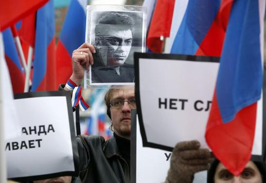 People hold placards to commemorate Kremlin critic Boris Nemtsov, who was shot dead on Friday night, in central Moscow March 1, 2015.   REUTERS-Sergei Karpukhin
