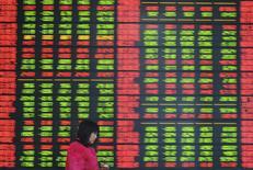 Женщина в брокерской конторе в Фуяне. 25 февраля 2015 года. Азиатские фондовые рынки выросли в понедельник благодаря снижению процентных ставок китайским центробанком. REUTERS/China Daily