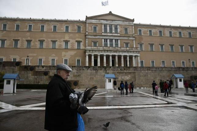 A man feeds pigeons in front of the parliament building in Athens, February 23, 2015.  REUTERS/Alkis Konstantinidis