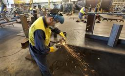 A Westralian Engineering Services worker uses a grinder in one of the company's workshops near Perth October 20, 2011. REUTERS/Ron D'Raine