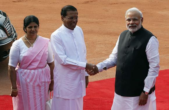 Sri Lanka's President Mithripala Sirisena (C) shakes hands with Indian Prime Minister Narendra Modi (R) as his wife Jayanthi Sirisena looks on during Sirisena's ceremonial reception at the forecourt of India's Rashtrapati Bhavan presidential palace in New Delhi February 16, 2015. Sirisena is on a four-day state visit to India. REUTERS/Adnan Abidi