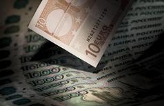 Купюры валют евро и рубль в Москве 17 февраля 2014 года. Рубль утром четверга вырос к евро, дешевеющему по всем фронтам  перед сегодняшним заседанием ЕЦБ, и торгуется с минимальными изменениями к доллару, обновляющему 11-летние максимумы на форексе.  REUTERS/Maxim Shemetov