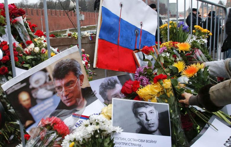 People lay down flowers at the site, where Kremlin critic Boris Nemtsov was murdered on Friday night, during a march to commemorate him in central Moscow March 1, 2015. REUTERS/Tatyana Makeyeva