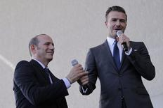 Don Garber (L) exchanges working microphones with David Beckham  at a news conference in Miami, Florida February, 5, 2014.     REUTERS/Andrew Innerarity